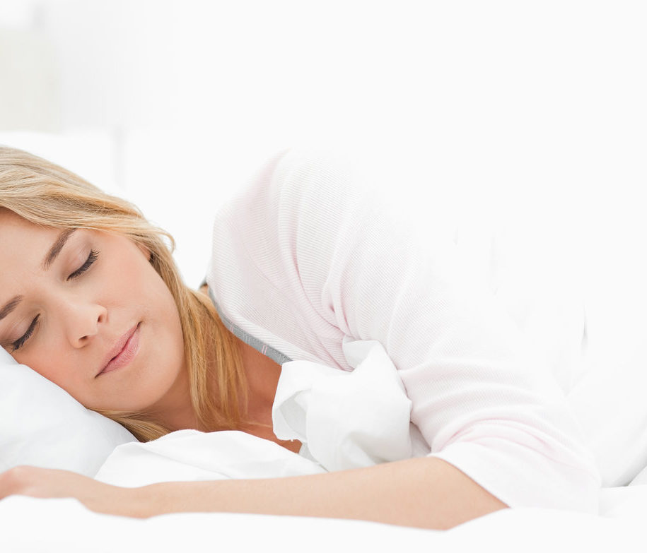 Woman sleeping in bed, with her arm resting slightly in front of her